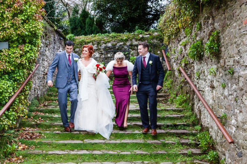 Bridal party going up a moss covered staircase