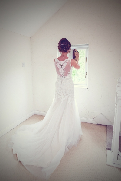 Full length photo of bride in her dress in an all white room at Barnabrow House