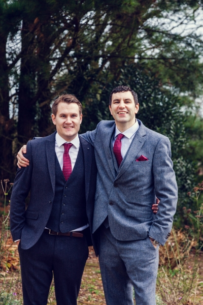 Groom and Best man pose for a photo in the woods