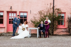 Bridal party including flower girl in front of pink pub