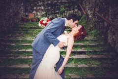 Groom dips his bride for a kiss on a moss covered staircase