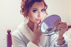 Bride looks at the camera while checking her reflection in the mirror