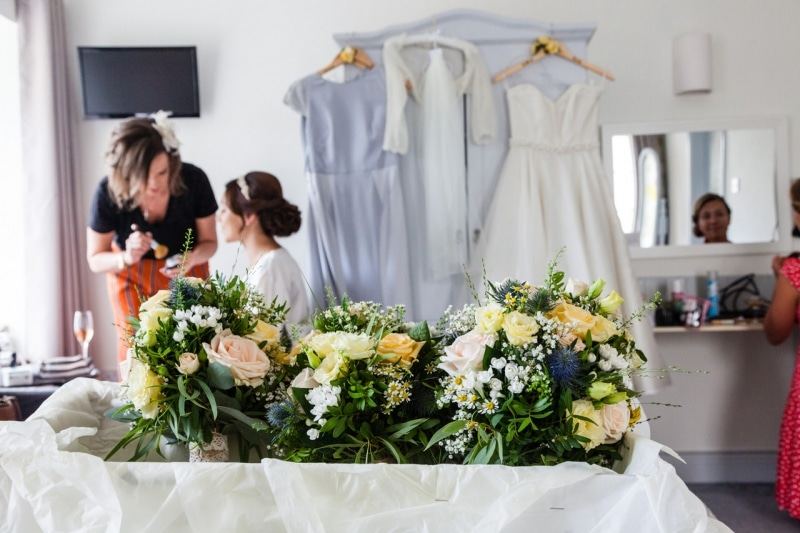 Bride getting ready in the Emmet Hotel Clonakilty with her bouquets in the foreground