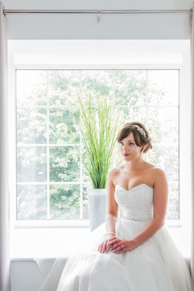 Bride sits on the windowsill at Emmet Hotel Clonakilty
