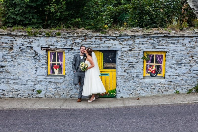 Bride and groom in front of a painted wall in Ring, Clonakilty