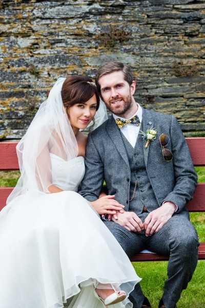 Bride and groom sitting on a red bench in Ring, Clonakilty