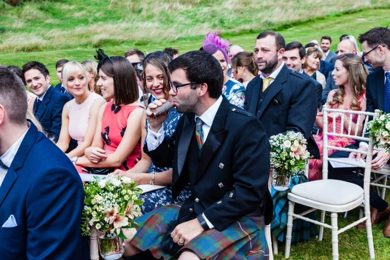 man seated outside sipping from his hip flask waiting for the wedding to start at Fernhill House Hotel