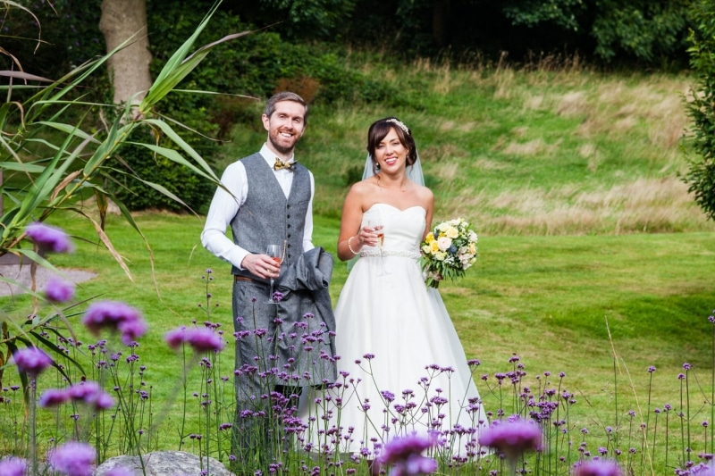 Bride and groom walk through the garden at Fernhill House Hotel