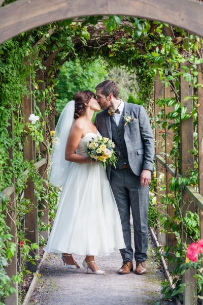 Bride and groom kiss in the garden at Fernhill House Hotel