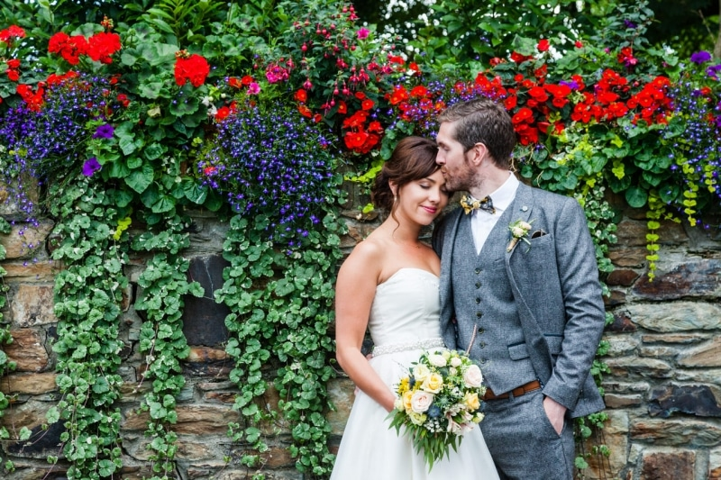 groom kisses bride on the forehead in front of a wall of flowers at Fernhill House Hotel