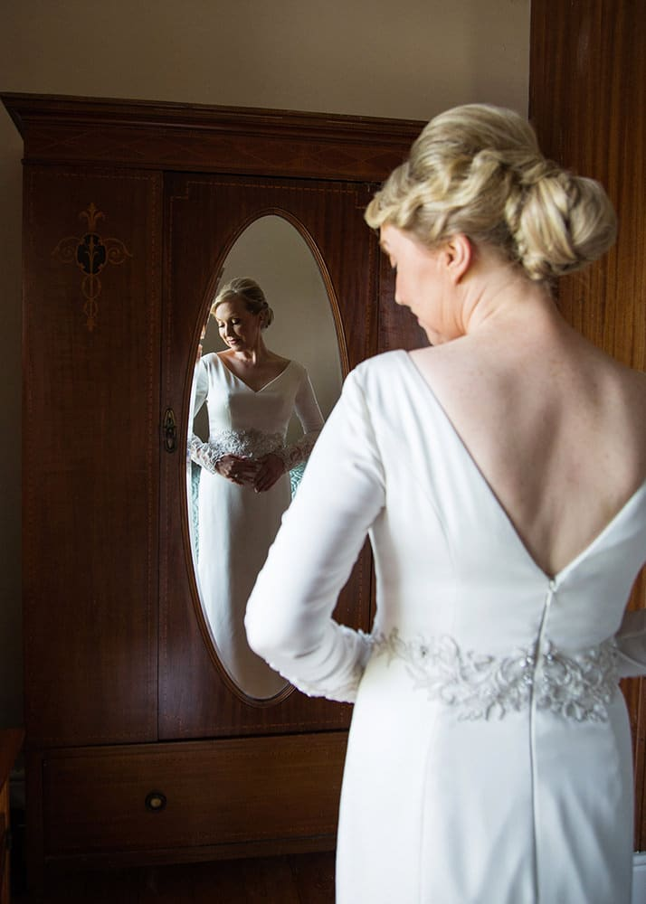 Bride reflected in mirror from the back - the detail of the v-back wedding gown