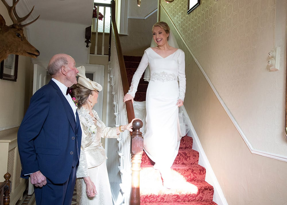 Bride descends the stairs while her parents wait at the bottom to greet her