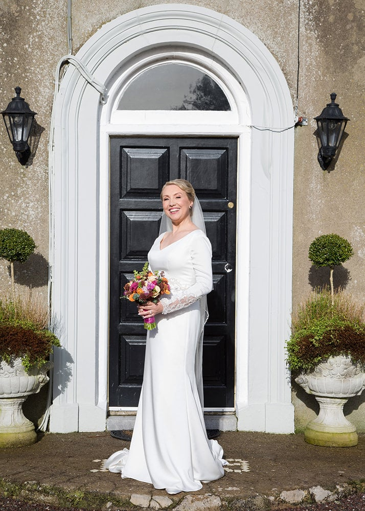 Bride posing with her bouquet in front of a black door
