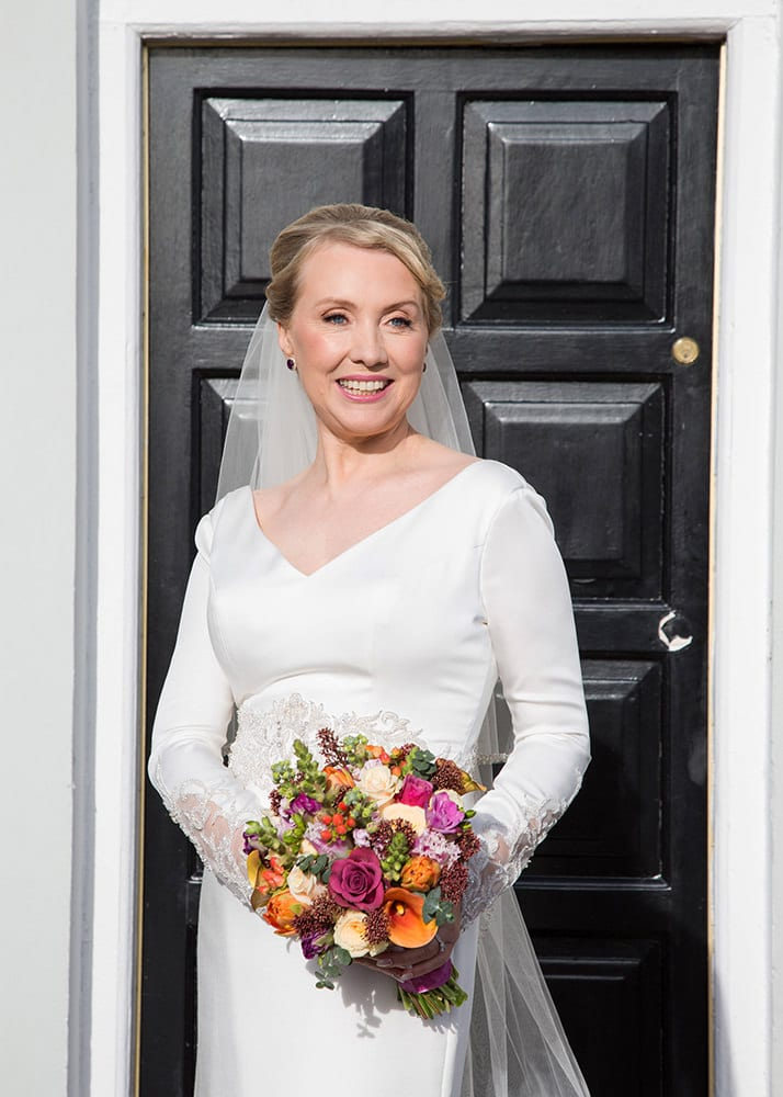 Closeup of bride and her bouquet in front of black Georgian door