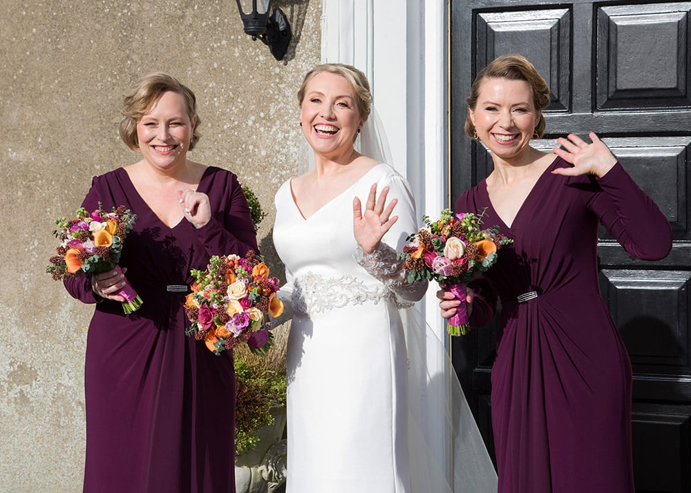 Bride and her bridesmaids in deep reed  pose with their bouquets