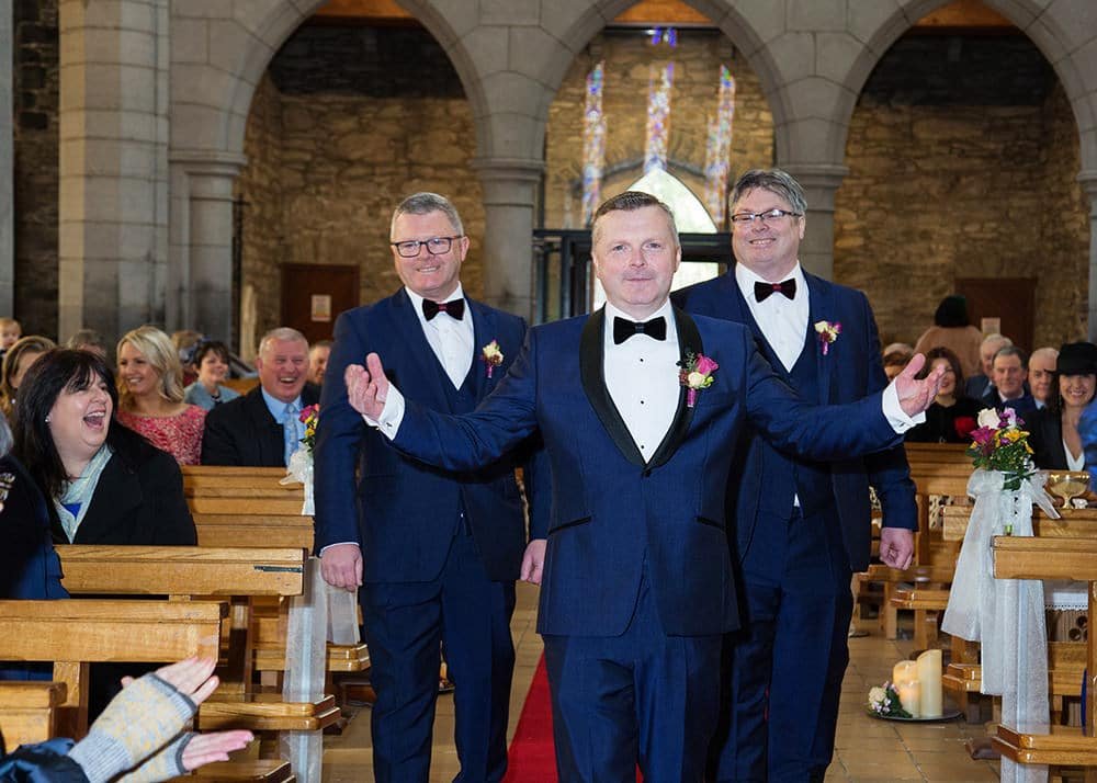 Groom and groomsmen smile from the aisle of the church while guests look on